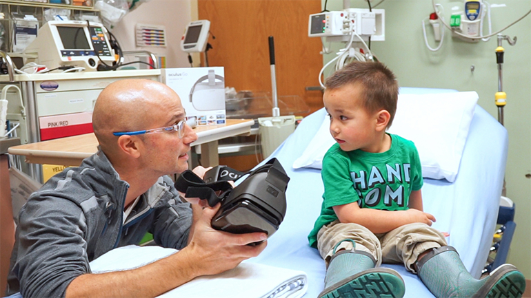 1ea7ce7a0984 VR in the ER. Peace Arch Hospital emergency physician Dr. Amir Behboudi  explains how virtual reality goggles work to a pediatric patient.